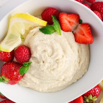 Overhead on a close up on a bowl filled with a vegan mascarpone cheese. There are strawberries and raspberries into the bowl as well as lemon slices around the bowl.