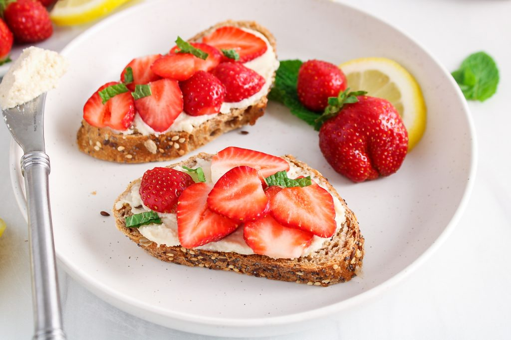 Front angle view on 2 pieces of bread garnished with a vegan mascarpone spread and topped with sliced berries and mint. There is a butter knife against the side of the plate with more of the mascarpone as well.