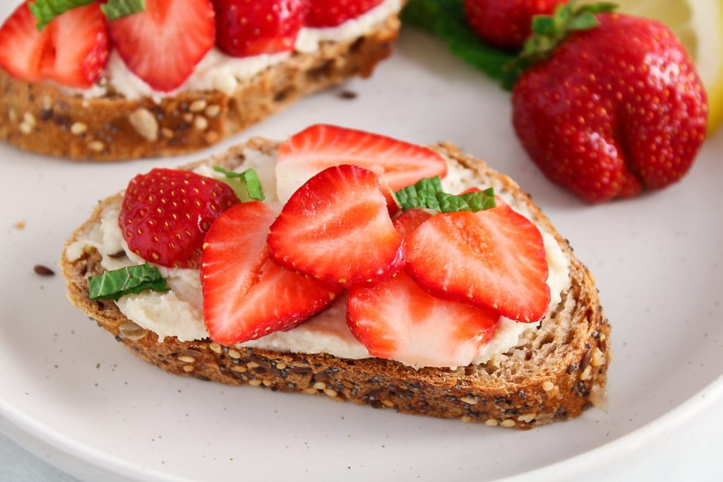 Close up on a piece of bread garnished with a vegan mascarpone spread and topped with sliced berries and mint. You can see more berries in the background as well.