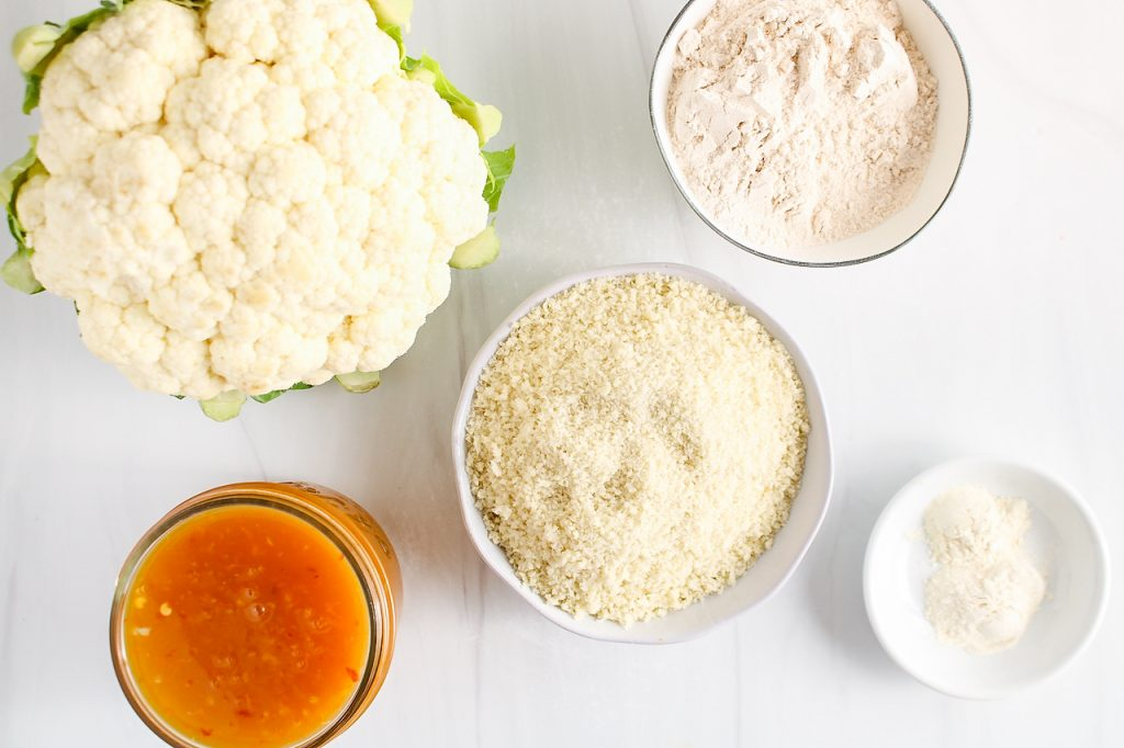 Showing are the ingredients needed to make this recipe: cauliflower, homemade orange sauce, flour, panko breadcrumbs and spices.