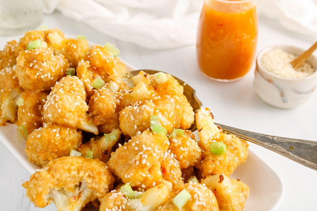 Front angle view on a pile of spicy orange cauliflower bites that are on a large rectangular white plate. There is a large serving spoon on the side as well as more orange sauce and sesame seeds in the background.