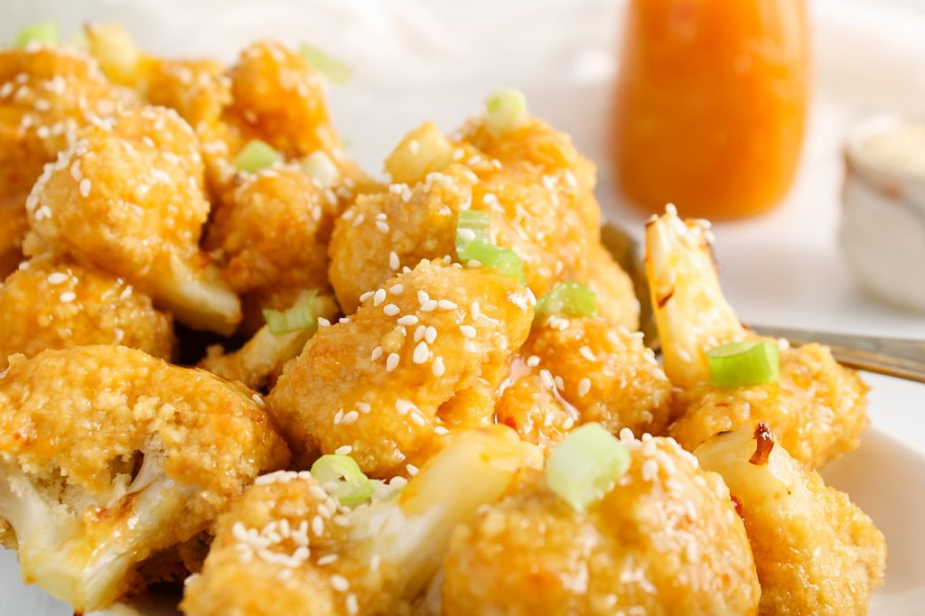 Close up on a pile of spicy orange cauliflower bites that are on a large rectangular white plate. There is a large serving spoon on the side as well as more orange sauce and sesame seeds in the background. There is a focus on the top cauliflower bite to show the silky orange sauce texture.