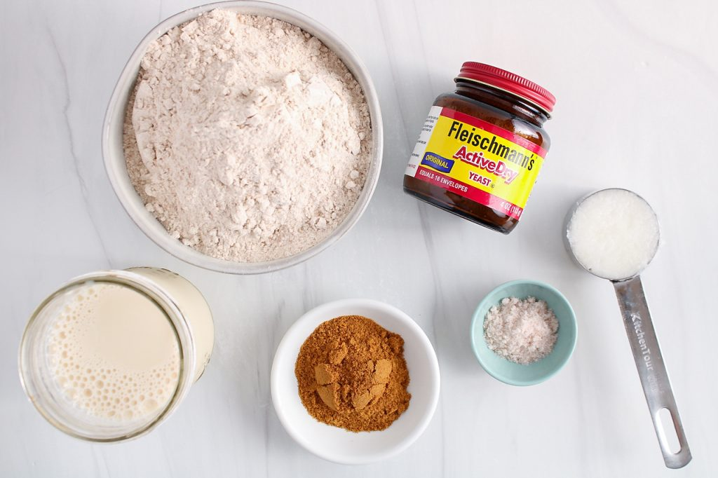 Showing are the ingredients needed to make this recipe: flour, yeast, vegan milk, coconut sugar, salt and coconut oil.
