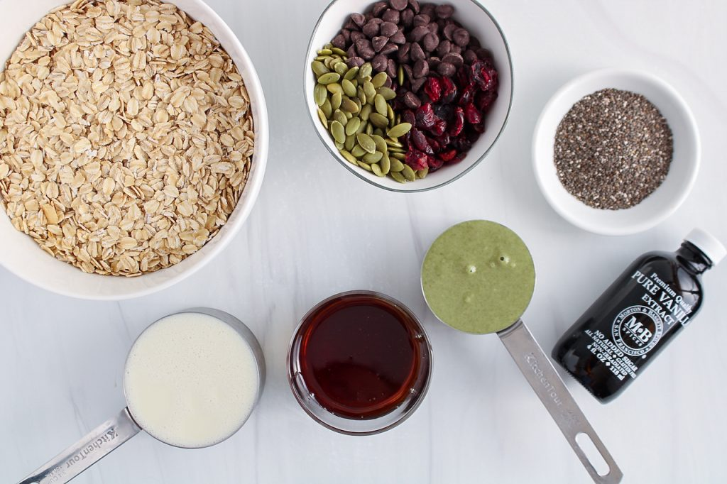 Overhead view showing the ingredients needed to make this recipe: rolled oats, pumpkin butter, vanilla extract, vegan milk, maple syrup, chia seeds, cranberries, pumpkin seeds and chocolate chips.