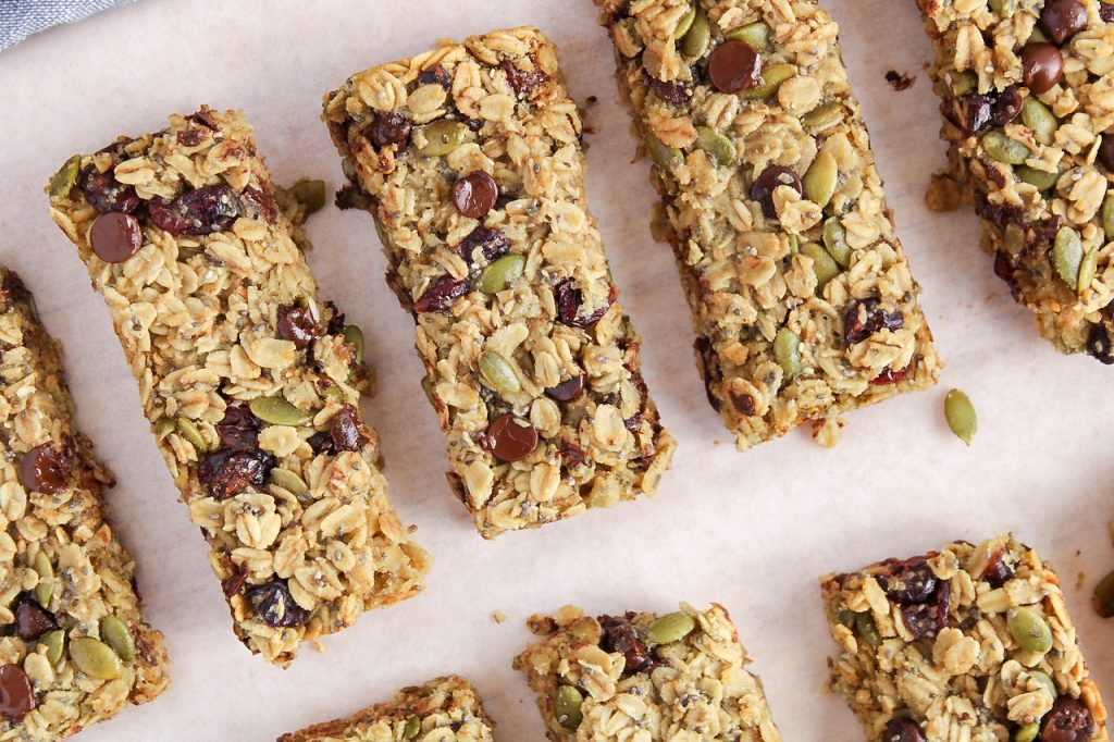 Overhead view on a few homemade nut-free granola bars place on a parchment paper covered wooden board. You can see nicely the ingredients within the bars being oats, chocolate chips and cranberries.