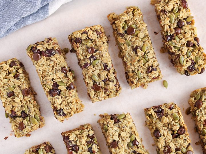 Overhead view on a few homemade nut-free granola bars place on a parchment paper covered wooden board. You can see nicely the ingredients within the bars being oats, pumpkin seeds, chocolate chips and cranberries.