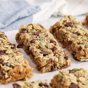 Front angle view on a few vegan nut-free granola bars filled with chocolate chips and cranberries that are placed on a wooden board covered with parchment paper.