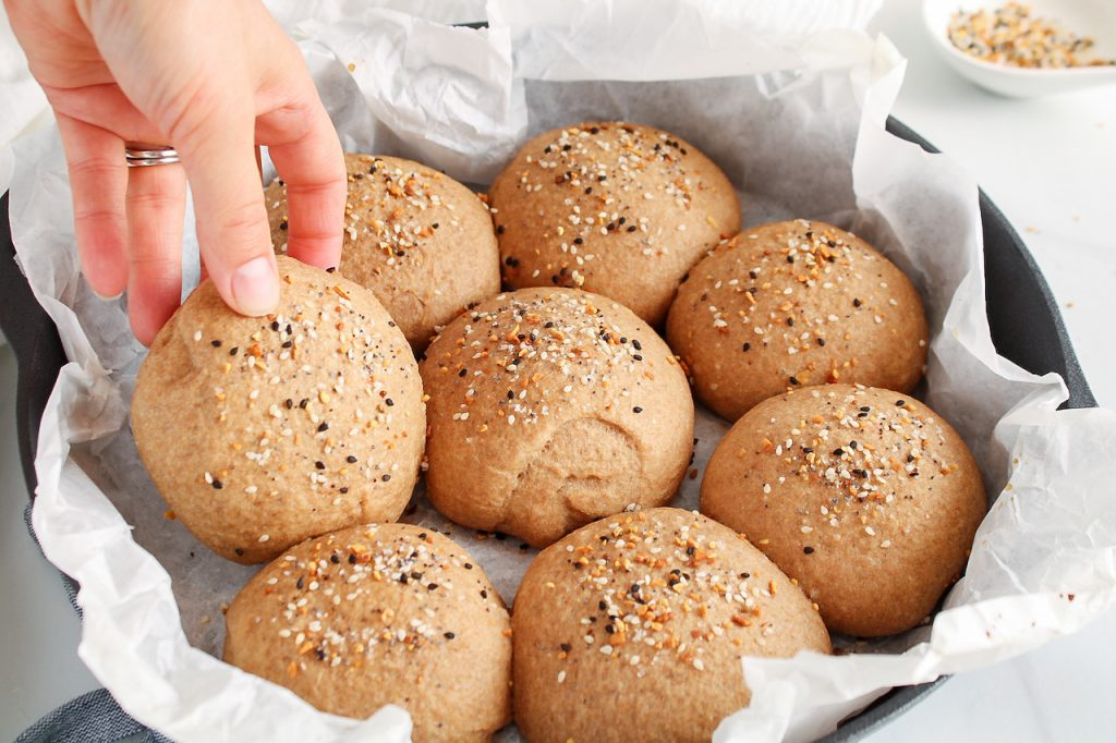 Front angle view on a few healthy vegan buns that are still in the cast iron pan used to bake them while you can see a hand that's grabbing one of the buns. The buns are also garnished with everything bagel seasoning.