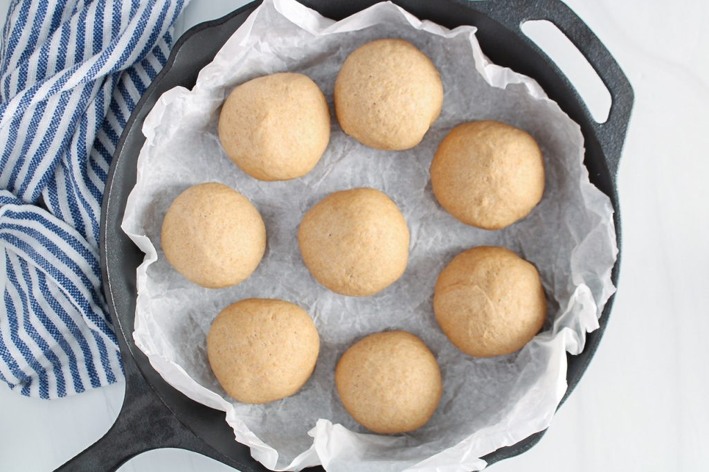 In process picture: There are 8 small balls of dough placed in a cast iron pan that was first covered with parchment paper.