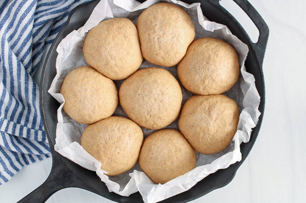 In process picture: There are 8 small balls of dough placed in a cast iron pan that was first covered with parchment paper. The balls slightly touch to each other.