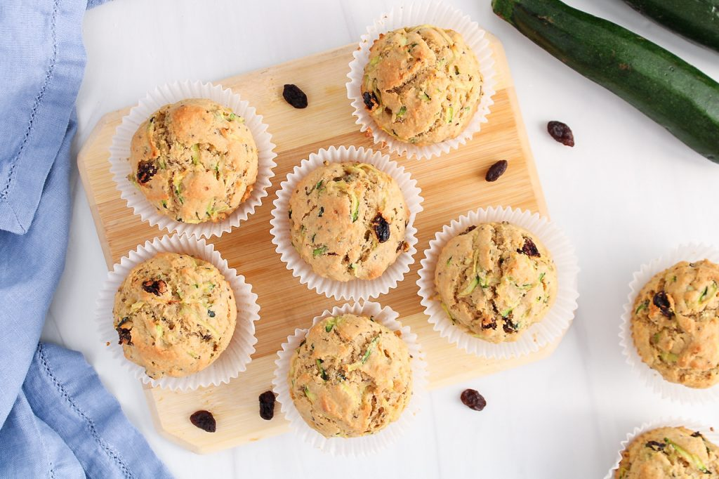 Overhead view on a few vegan zucchini raisin muffins that are placed on a wooden board. There are a few raisin around the muffins and a zucchini as well as a blue hand towel.