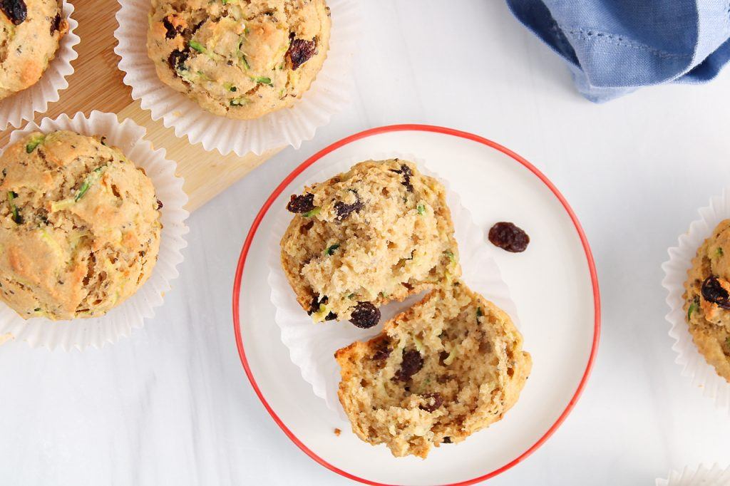 Overhead view on a vegan zucchini riasin muffins that was opened up and placed on a plate. There is a close up on its interior to shows texture and there are more muffins beside the plate as well.