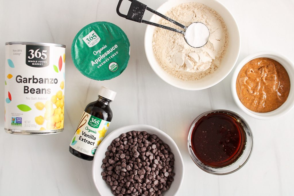 Showing are the ingredients needed to make this recipe: chocolate chips, vanilla extract, garbanzo beans, apple sauce, flour, baking powder, almond butter and maple syrup.