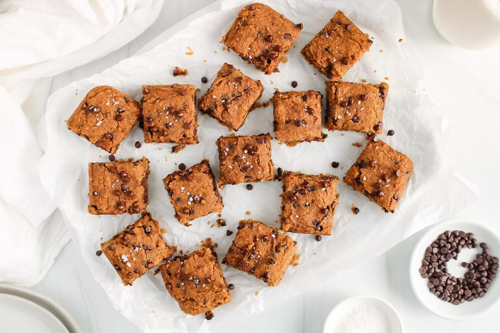 Overhead view on a few squares of a vegan chickpea blondies that are placed on a large plate covered with parchment paper. There is a bowl containing chocolate chips on the side as well as a few serving plates.