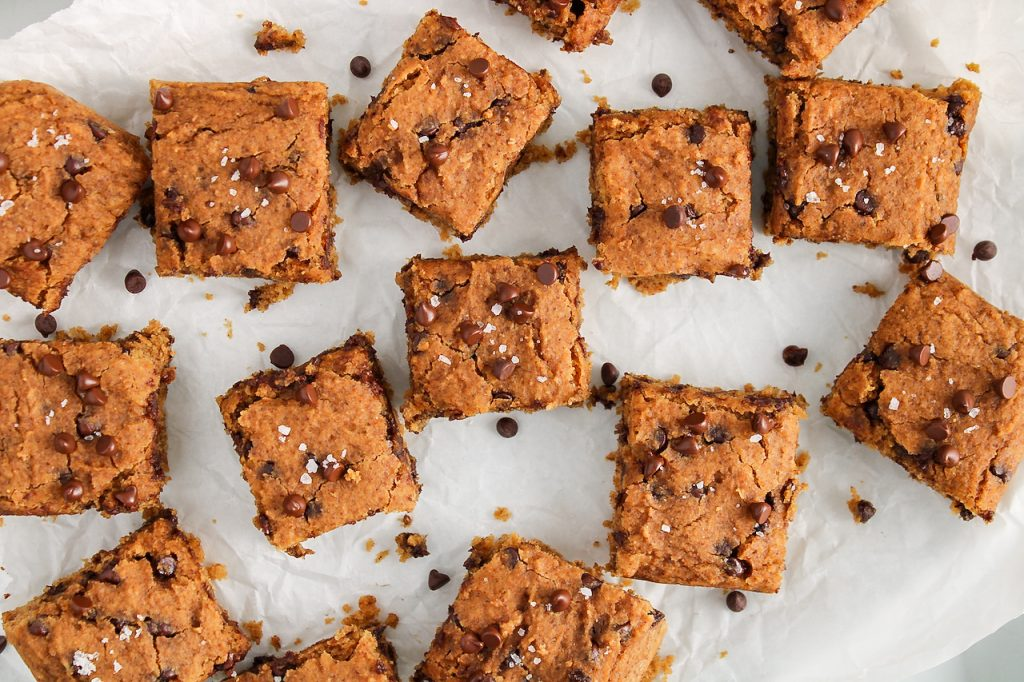 Overhead view on a close up of a few squares of a vegan chickpea blondies placed on a large plate covered with parchment paper. There are a few chocolate chips surrounding the squares as well. The squares are also garnished with sea salt.
