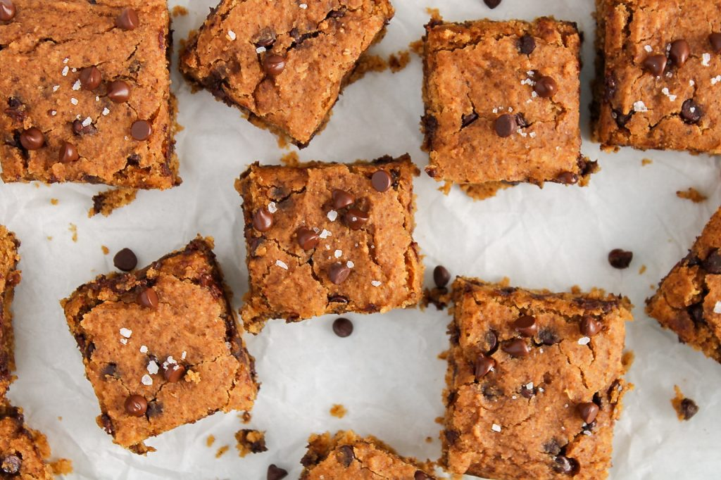 Overhead view on a vegan chickpea blondies squares from a plate that contains more of the square. This a close up picture so you can see the texture well.