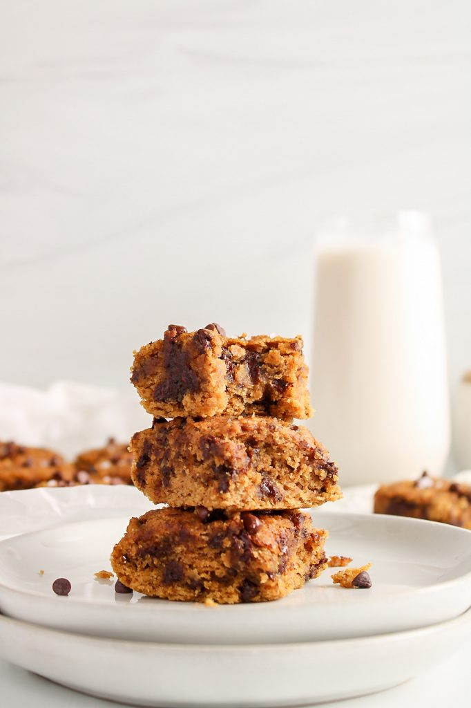 Front view on 3 squares of chickpea blondies that are on top of each other. The top square has a bite taken off to show the texture.