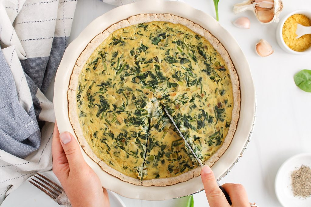 Overhead view on a vegan spinach quiche that's being sliced. There are on the side a hand towel, garlic, nutritional yeast in a bowl and black pepper.