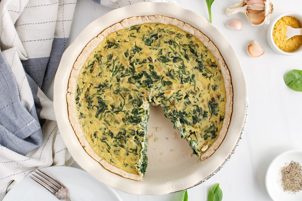 Overhead view on a vegan spinach quiche with a slice that was taken off. There are on the side a hand towel, garlic, nutritional yeast in a bowl and black pepper.