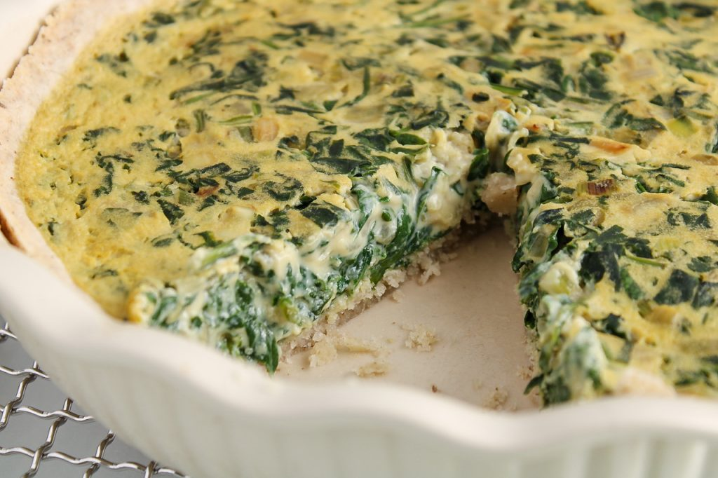 Front angle view on a vegan spinach quiche with a slice taken off. There is a close up on the middle portion to show the creamy texture of the quiche.