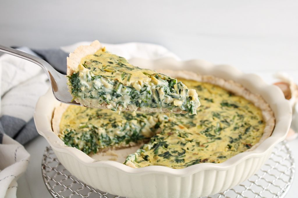 There is a slice of a vegan spinach quiche that's being hold and close to the camera. You can see in the background the whole vegan spinach pie as well as a white and blue hand towel.