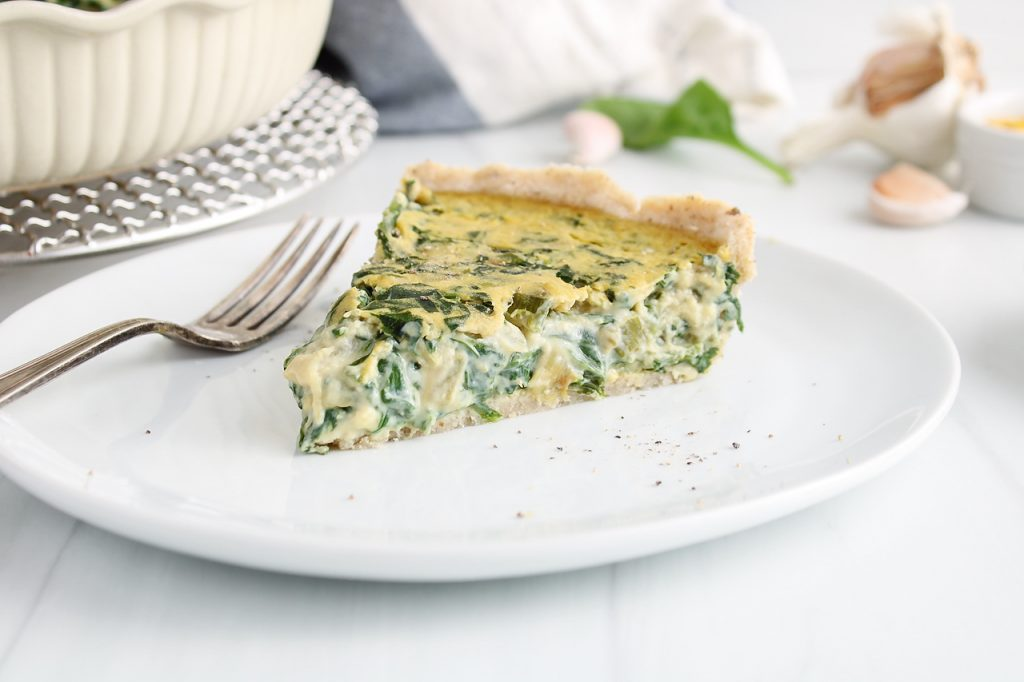 Front view on a slice of vegan spinach quiche that's placed on a white plate with a fork on the side. There is a bigger spinach pie in its dish in the background.