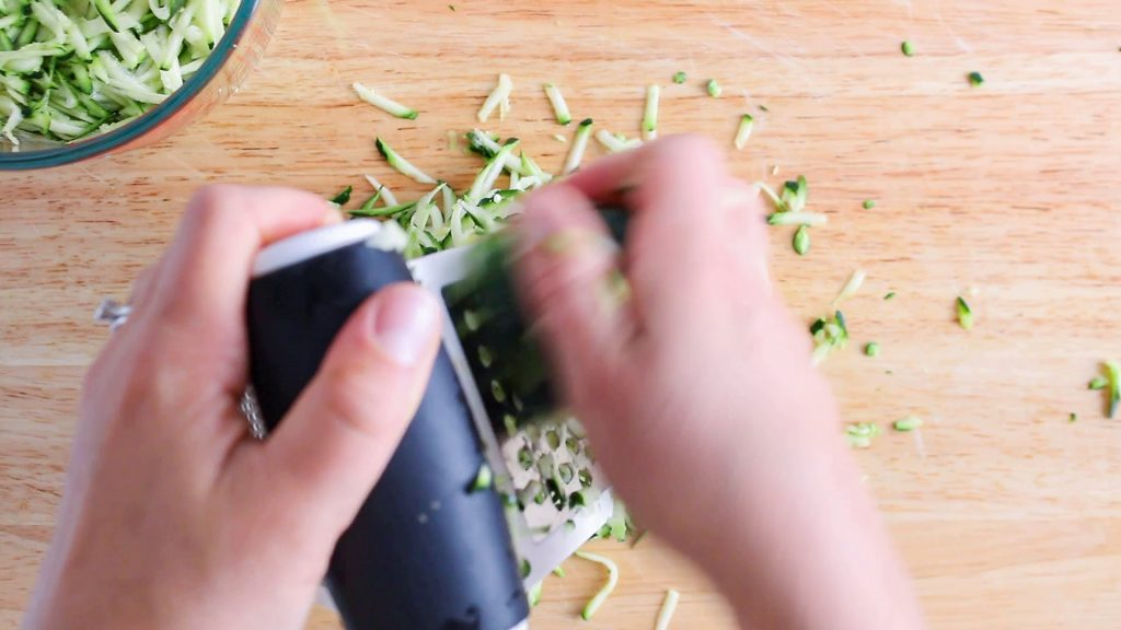 In process picture: there are 2 hands that are grating zucchini using a hand-grater.