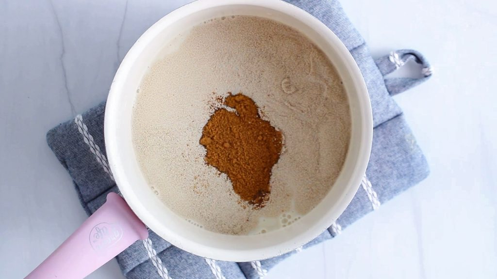 In process picture: Overhead view on a small pot containing vegan milk with coconut sugar and yeast.