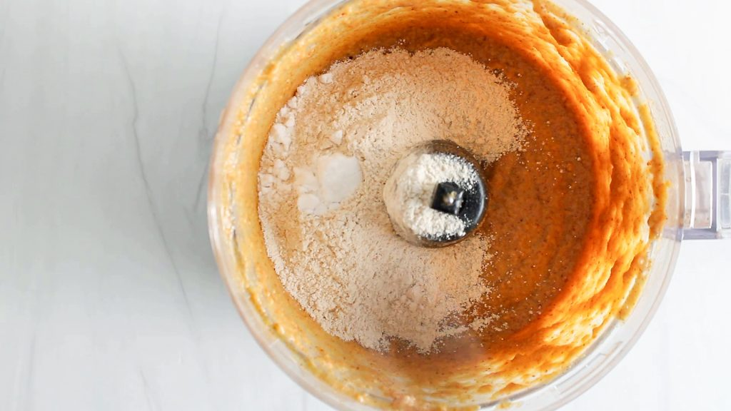 In process picture: Overhead view on a food processor containing a creamy beige mixture that's topped with a flour mixture.