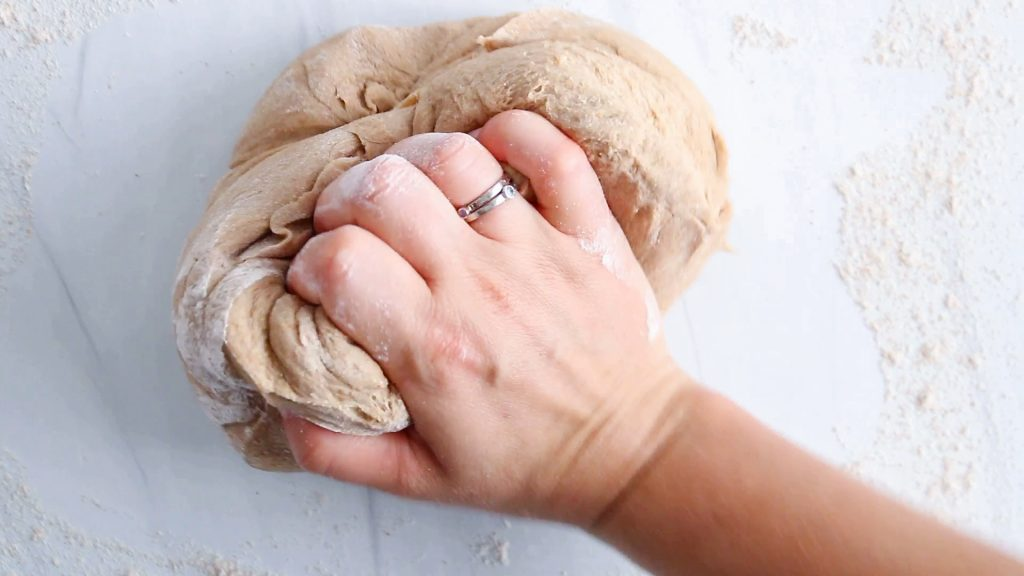 In process picture: there is a hand that kneading a dough on a table.