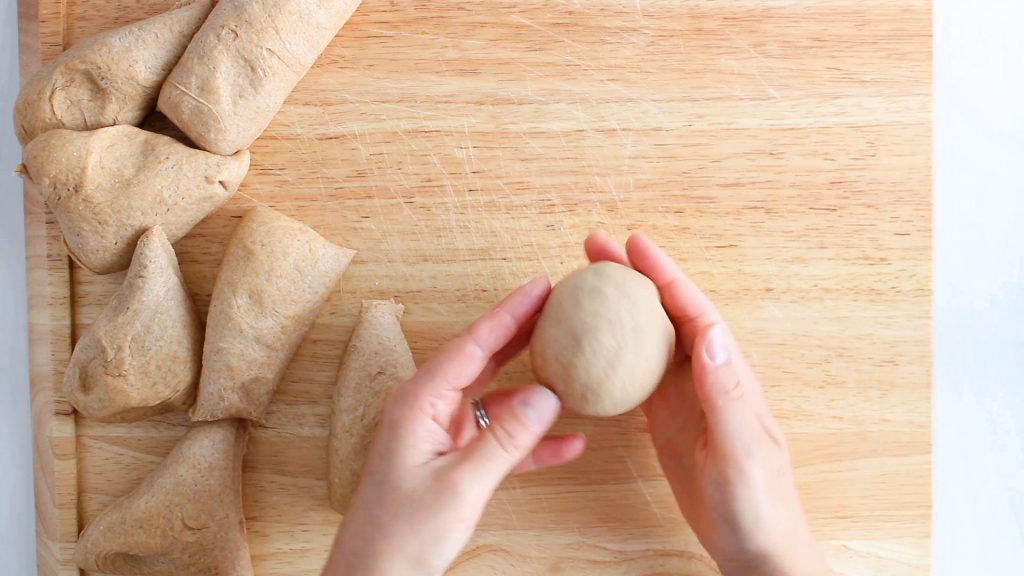 In process picture: you can see 2 hand that are shaping a piece of dough into a ball.