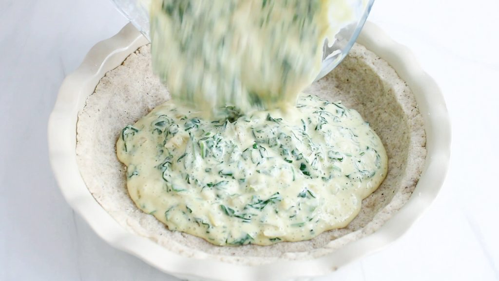 In process picture: showing is a blender that's pouring a creamy spinach mixture over a pie crust.