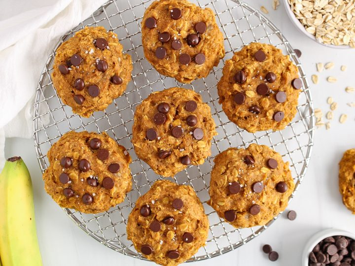 Overhead view on a circular cooling rack containing a few vegan pumpkin chocolate chip cookies. There are bananas, rolled oats and chocolate chips on the side.