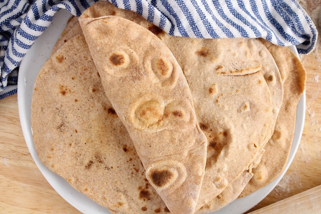 There are a pile of vegan whole wheat tortillas made from scratch piled on a plate with a damp hand towel over half covering them. The top tortilla is half folded to show how soft the tortillas are.