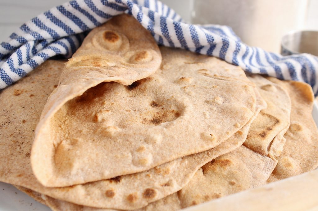Front angle view on a pile of vegan tortillas that are on a plate and covered with a white and blue hand towel. The top tortilla is folded to show its nice and soft texture.