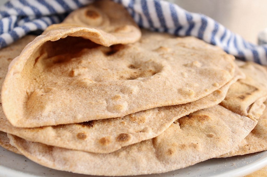 Close up on a few homemade vegan tortillas that are on top of each other and covered with a white and blue hand towel. The top tortilla is folded to show its fluffy texture.