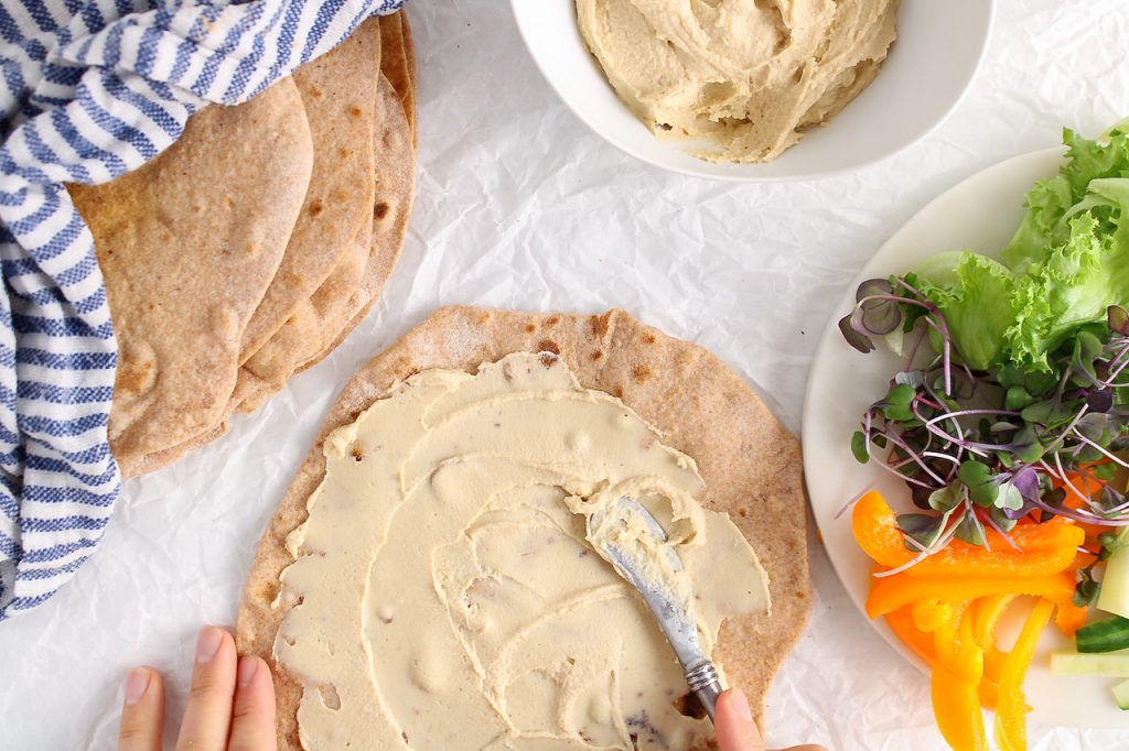 Overhead view on a homemade vegan tortilla that has some hummus being spread over. There are more freshly made tortillas on the side as well as a plate filled with produce.