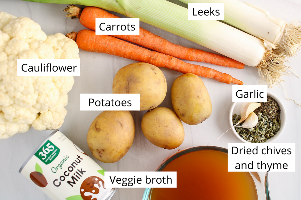 Showing are the ingredients needed to make this recipe: cauliflower, carrots, potatoes, garlic, leeks, can of coconut milk, veggie broth and dried herbs.