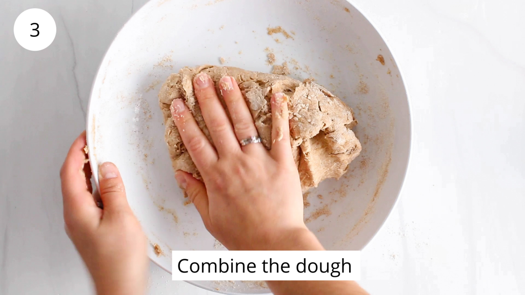 In process picture: there is a hand that's combining a dough in a large white bowl.