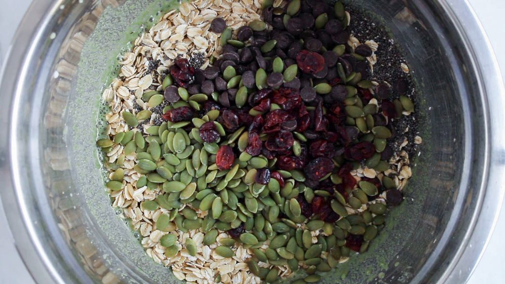 Overhead view on a large mixing bowl that contains oats, dried fruits, nuts and chocolate chips.