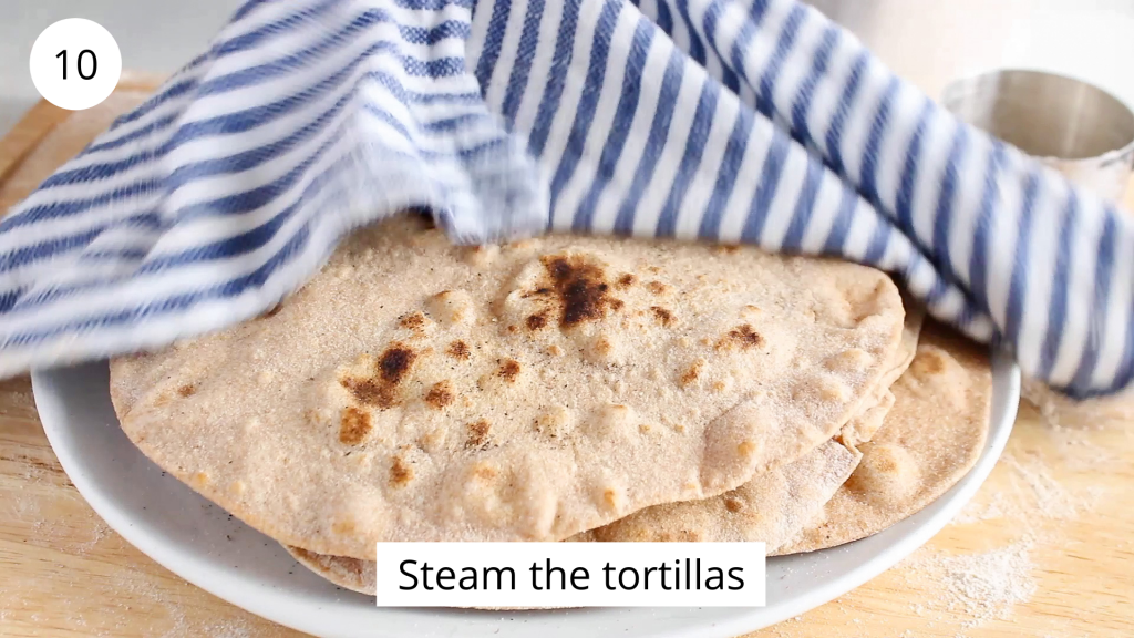 In process picture: there is a pile of freshly made tortillas that on a plate and covered with a damp hand towel.